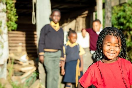 gente pobre: una linda chica africana con el pelo trenzado y una camisa de color rojo brillante que sonríe con confianza con sus hermanos en el backround cuidándola Foto de archivo