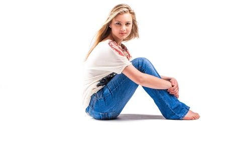 barefoot teens: a pretty teenage caucasion girl with blond hair and blue eyes sitting in the studio with blue jeans and an american printed shirt Stock Photo