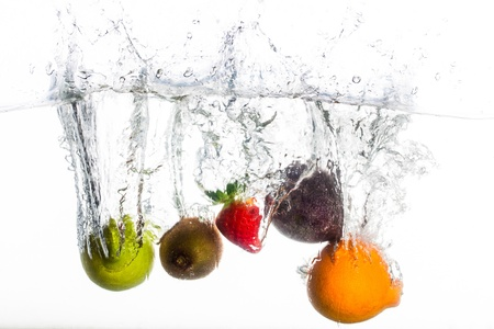 a lemon, kiwi, strawberry, granidilla and orange being dropped into clear fresh water. Stock Photo