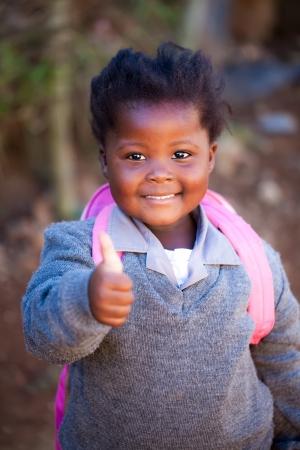 African children: cô gái trẻ Châu Phi với một ngón tay cái lên positiv trên đường đến trường trong một túi màu hồng và quần áo màu xám trường Kho ảnh