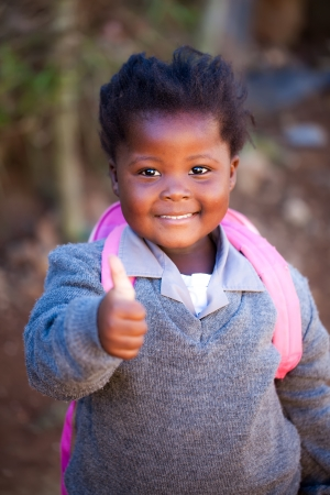 township: young african girl with a positiv thumb up on her way to school in a pink bag and gray school clothes