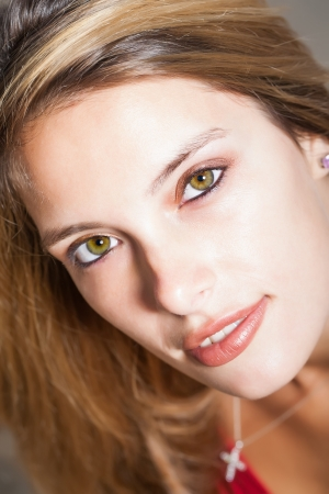 sneaky: close-up of a beautiful young cacasian womans content face with bright green eyes and a sneaky smile Stock Photo