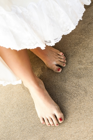 bare feet girl: a close-up on a dress being lift up to reveal slim sandy feet with red toenails Stock Photo