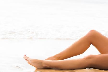 uñas pintadas: hermosas piernas delgadas caucásicos descansando en las aguas poco profundas en la playa con las uñas pintadas de color rojo