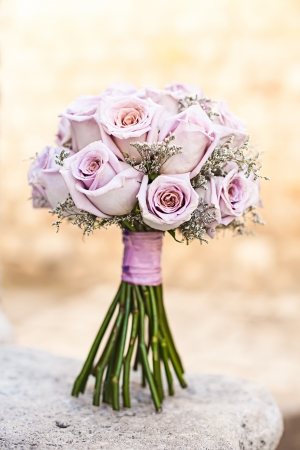 isolated purple wedding bouquet standing on a stone step