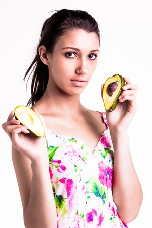 pretty caucasian brunette girl holding up cut avocado in her hands photo