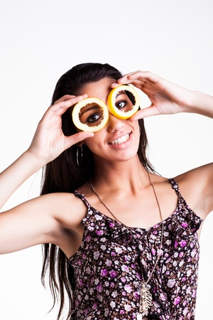 pretty caucasian brunette girl holding hollow lemon peels infront of her eyes smiling photo