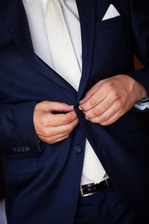 hankerchief: a groom wearing a tailored navy suit buttoning up Stock Photo