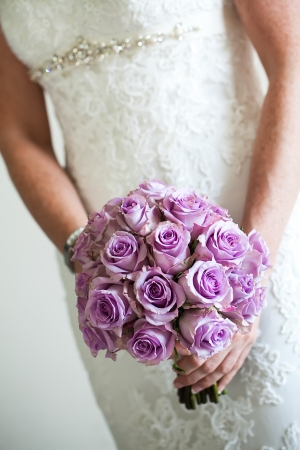 purple rose: cropped image of a bride holding her bouquet of purple flowers on her wedding day