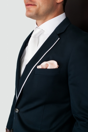 hankerchief: cropped image of the groom in a dark navy suit with white piping and a crisp white shirt and tie with a peach  hankerchief peeping out of his pocket
