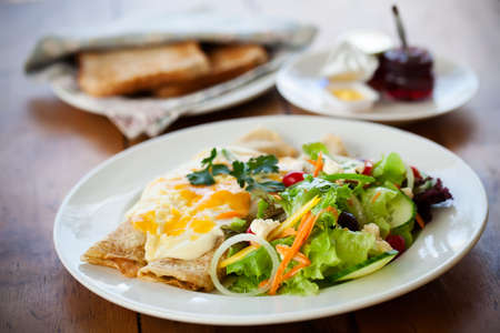 dribbled: two filled crepes dribbled with cheese sauce plated with a healthy salad and some toast with condiments in the background all on a wooden table