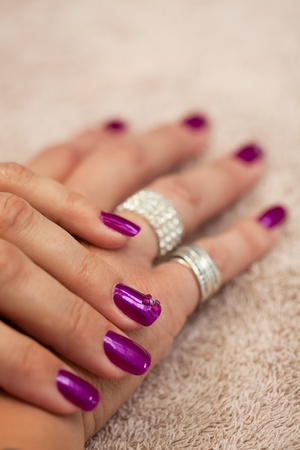 zoomed in: a close-up image of a pair of jeweled hands painted purple with bling on a cream towel