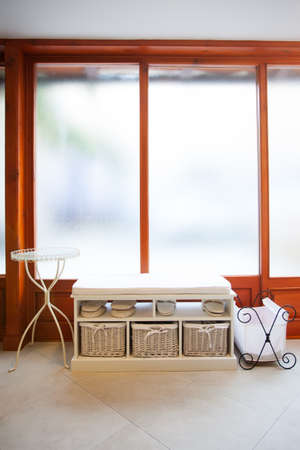 blasted: image of an open seating area holding spa slippers and backets with a round table and magazine holder against big sand blasted windows Stock Photo