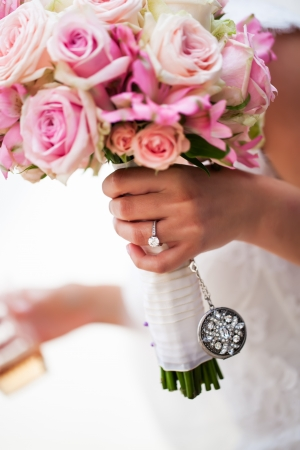 rosoideae: a cropped portrait of a brides hand holding her pink bouquet of roses with her engagement ring on her finger