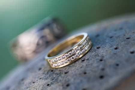 an image of the brides wedding ring designed with two rows of tiny diamonds in gold with the grooms ring in the background resting both on a stone slab Stock Photo