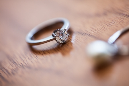 image of the brides traditional engagement ring resting on the wooden surface