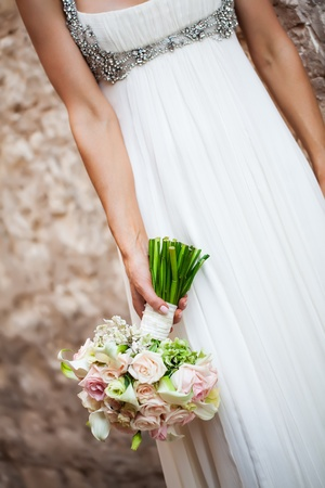 a cropped image of a bride holding her bouquet of roses upside down in her hand Stock Photo