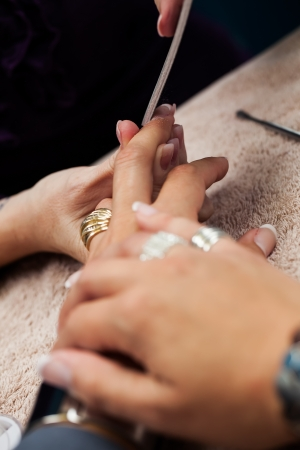 jeweled: close-up image of a pare of jeweled fingers being filed in a nail spa