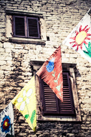close-up image of home painted flags hung up in the streets of sibenik for celebration photo