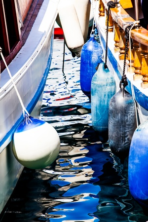 cropped off: a cropped image of the  port and starboard of two boats close to each other with buoys hanging off the side Stock Photo