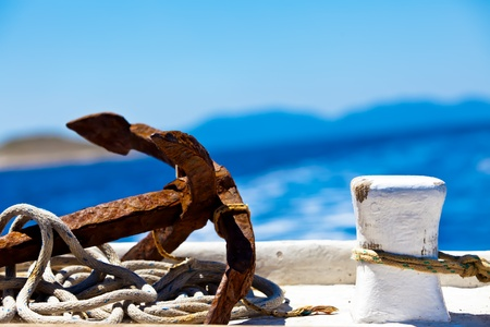 een close-up foto van een rustieke anker geplaatst naast een docking pilaar omringd door touw in de haven