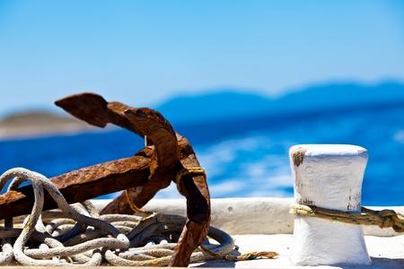 une image en gros plan d'une ancre rustique placé à côté d'un pilier d'accueil entouré de corde dans le port