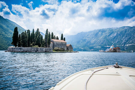 image of the bow of a boat cruising through the canal surrounded by beautiful mountains and odd small islands with chapels on them Stock Photo