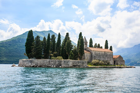 an old stone church surrounded by big trees isolated on a small island in the canals of the island Standard-Bild