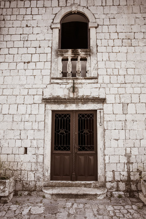 a portrait image of an old double wooden door with a chapel design window above it in an old stone wall