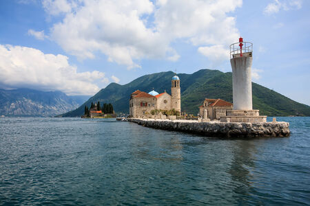 two small islands with old historic church chapels on them in the canals between the beautiful mountains of the main island