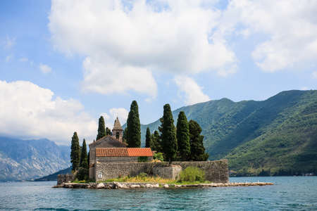 an old historic chapel on a small islands with trees surrounding it in privacy on the canal going through the mountains of the big island Standard-Bild