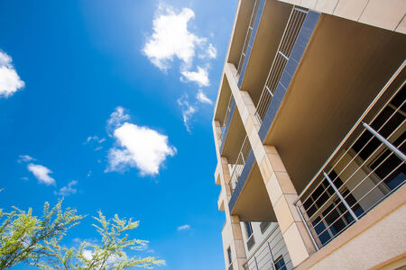 a worms eye view of a tall building stretching up to the bright blue sky and a tree peeking out from below