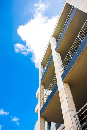 an image of a tall building reaching up into the bright cloudy sky Stock Photo