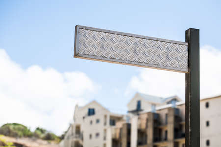 an image of a textured steel street sign with apartment buildings standing in the background