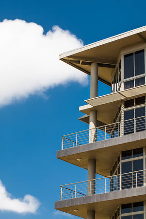 an image of a cropped tall storey buildings balconies with a bright blue sky in the background