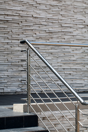 an image of steel railings following along the passage and steps with a gray stone wall in the background Stock Photo