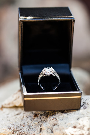image of the brides diamond wedding ring in a gold and navy box resting on a rock