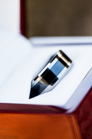 a close-up image of the grooms black and silver wedding ring in a white leather and wooden casing
