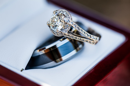 close-up image of the bride and grooms wedding rings overlapping together in a white leather and wooden casing Standard-Bild