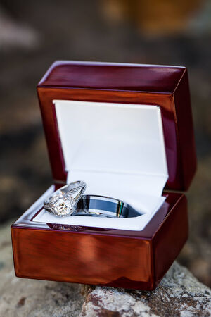 an image of the bride and grooms wedding rings together in a white leather and wooden casing