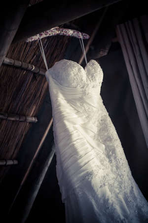a moody image of the brides detailed wedding dressed hanging from the thatched roof Standard-Bild