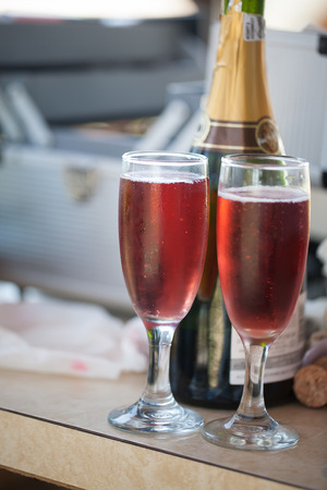 two glasses of bubbly pink champagne on a counter with the bottle in the background Standard-Bild