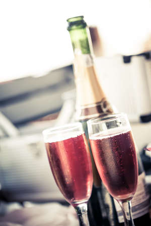 and soft image of two glasses filled with pink bubbly champagne with the bottle standing in the background