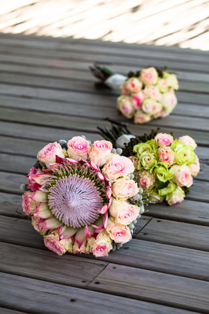 image of the bride and her bridesmaids bouquets lying on the wooden deck in the shade in a row