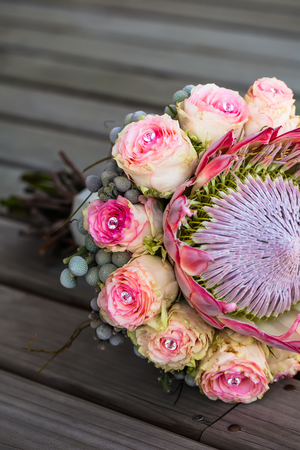 cropped image of a protea and rose bouquet resting on a wooden deck
