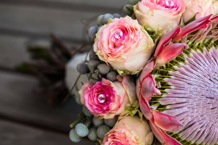 close-up cropped image of a protea and rose bouquet with crystal details