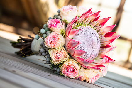 a king protea and detailed rose bouquet resting on a wooden deck Standard-Bild