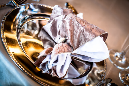 napkin ring: a cropped image of a champagne and white napkin in a napkin ring placed on a silver plate Stock Photo