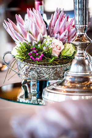 an image of a tables centerpiece of a detailed silver vase filled with wild flowers, roses and king proteas