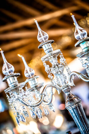 a cropped image of a silver   and crystal candle holder with lit glass candles
